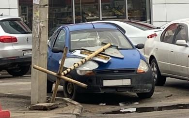 В Воронеже ветер уронил столб с дорожными знаками на автомобиль